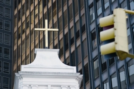 One of New York City's oldest Catholic Church sites sits prominently among the skyscrapers of Manhattan's financial district [Screengrab/Al Jazeera]