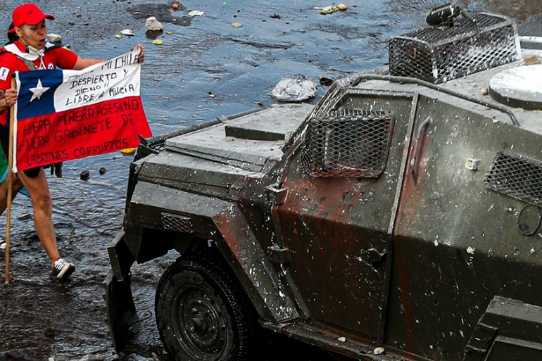 A demonstrator holds a Chilean flag towards an armored police vehicle during an anti-government march in Santiago, Chile [Esteban Felix/AP Photo]