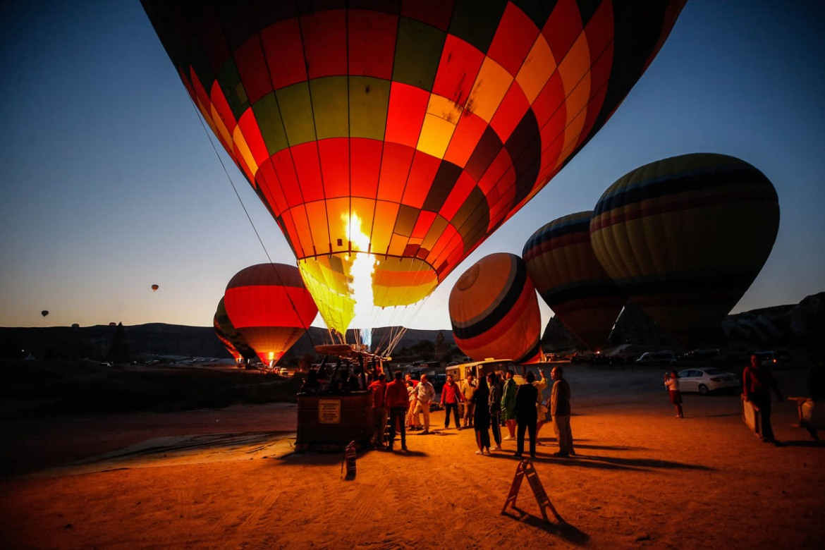 Tourists gather as the balloons are prepared before taking off. [Emrah Gurel/AP Photo]