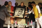 Prime Minister Narendra Modi, BJP President Amit Shah and the party's candidate Kiran Bedi hold a portrait of Gandhi during a campaign rally in New Delhi, India Jan 31, 2015 [File: Altaf Qadri/AP]