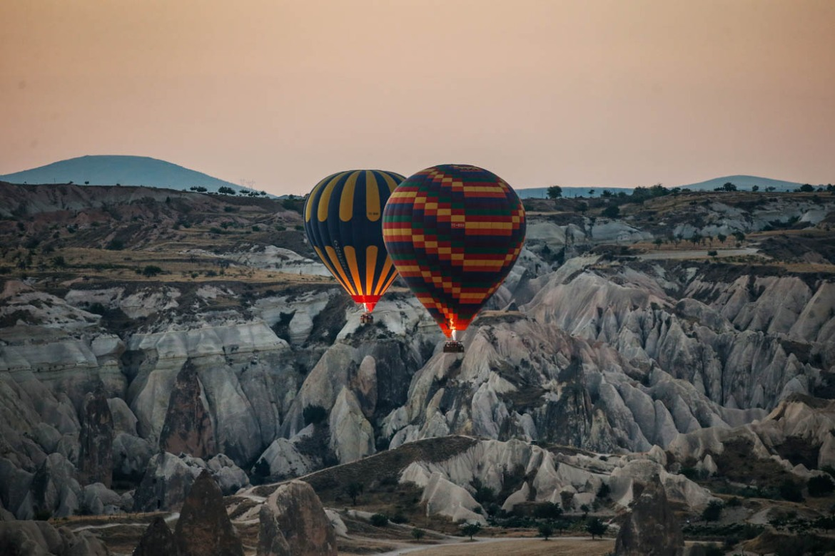 Hot air balloons rise into the sky above the 'fairy chimneys' of stone that are so soft that Byzantine Greeks carved subterranean cities out of them. [Emrah Gurel/AP Photo]