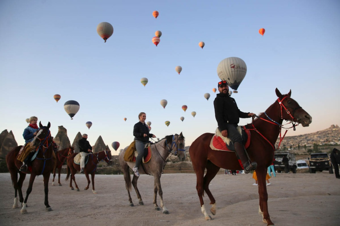 Visitors ride horses as hot air balloons glide over Goreme district during the early morning at the historical Cappadocia region. [Behcet Alkan/Anadolu Agency/Getty Images]