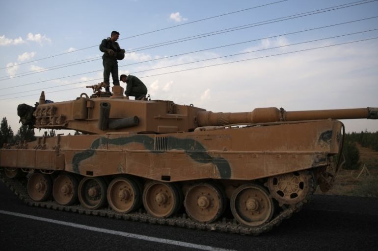Turkish soldiers stand atop of a tank as army vehicles move on a road near the Turkish border town of Ceylanpinar, Sanliurfa province, October 18, 2019 [Stoyan Nenov/Reuters]