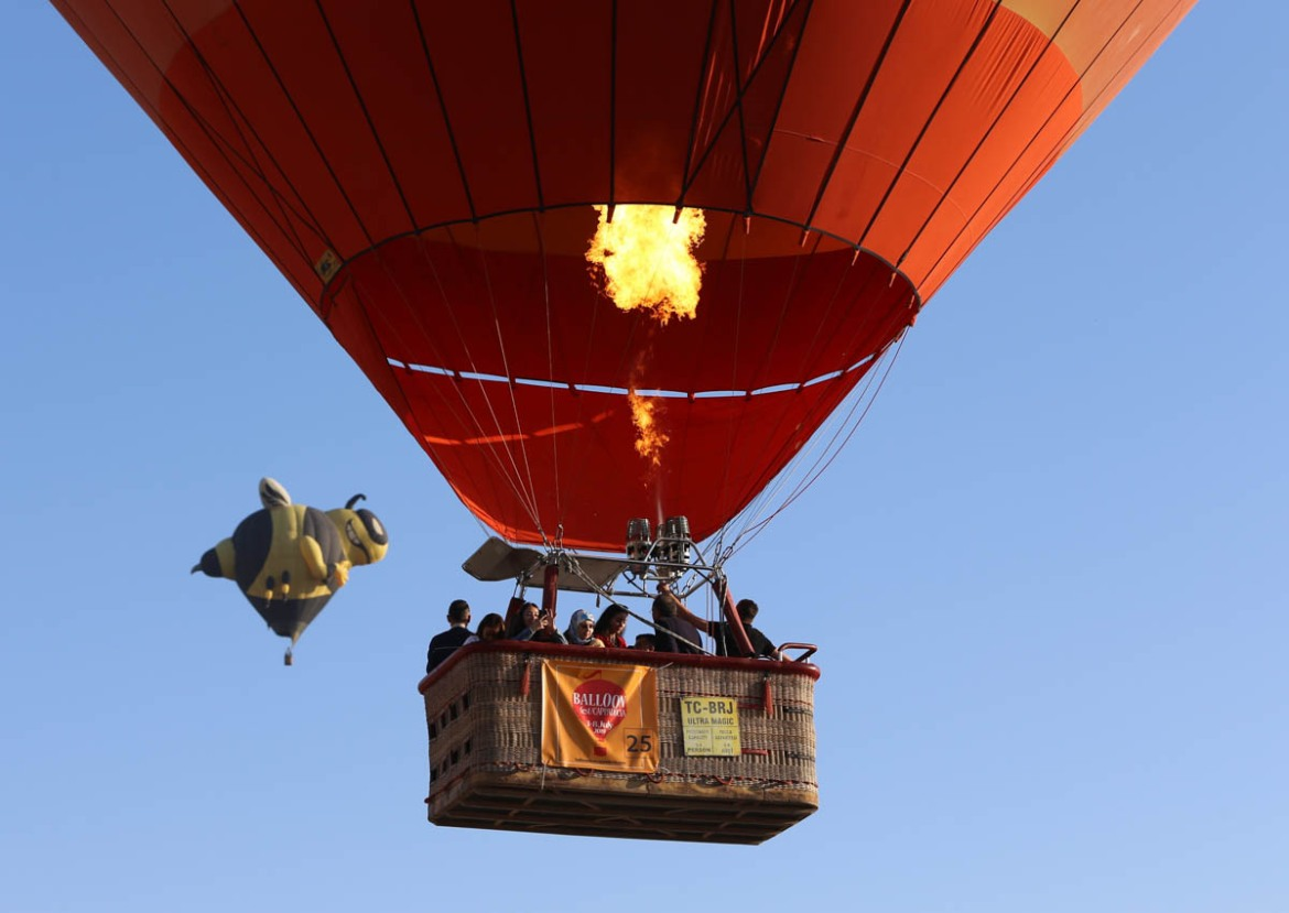 Hot air balloons in different shapes and sizes fly over the tourist hub. [Alpaslan Korukcu/Anadolu Agency/Getty Images]