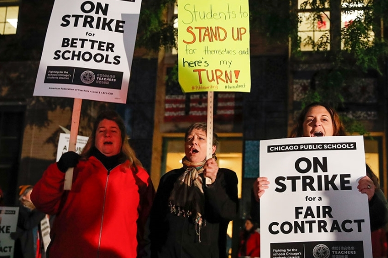 Striking teachers and supporters walk a picket line outside Peirce Elementary School on the first day of a strike by the Chicago Teachers Union [Kamil Krzaczynski/AFP]
