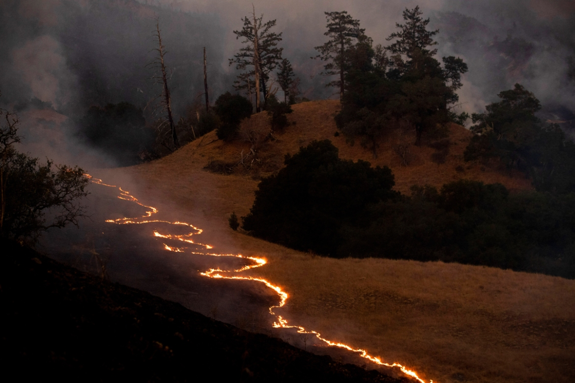 A line of fire snakes along a hillside as firefighters light backfires to slow the spread of the Kincade Fire in unincorporated Sonoma County, near Geyservillle. [Noah Berger/AP Photos]