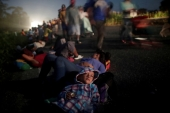 Migrants forming part of a caravan of thousands of people from Central America en route to the United States rest on the road in Mexico [File/Ueslei Marcelino/Reuters]