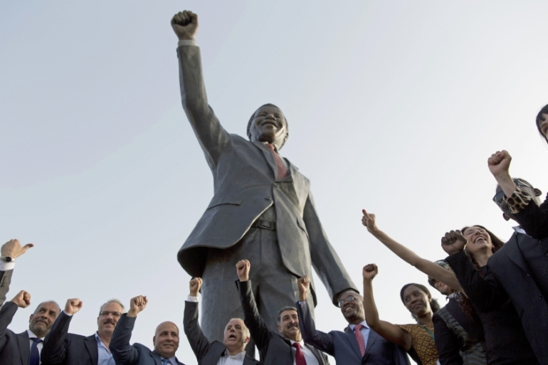 Palestinians pose for a picture with a sculpture of the first democratically elected South African President Nelson Mandela in the West Bank city of Ramallah, on April 26, 2016. [AP/Nasser Nasser]