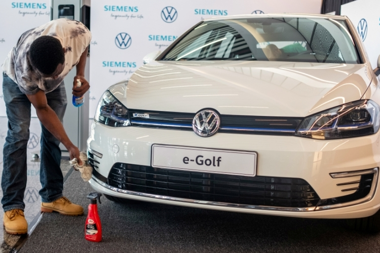 A worker cleans a Volkswagen e-Golf electric car during its launch for use in a new ride-hailing service in Kigali, Rwanda [Jean Bizimana /Reuters]