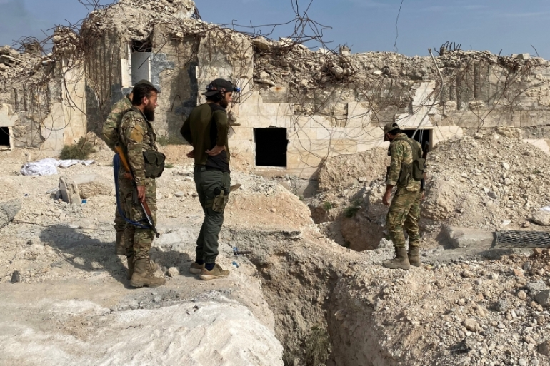 Turkey-backed Syrian fighters stand near underground tunnels said to be made by Kurdish fighters in Tal Abyad [Mahmoud Hassano/Reuters]