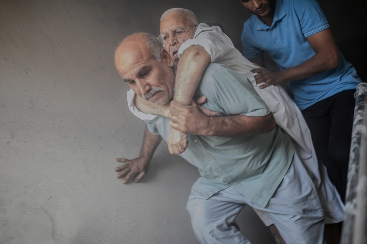 An elderly man is evacuated from a building in Akcakale, a Turkish town near the border with Syria, after it was hit by a mortar reportedly fired from within Syria. [Bulent Kilic/AFP]