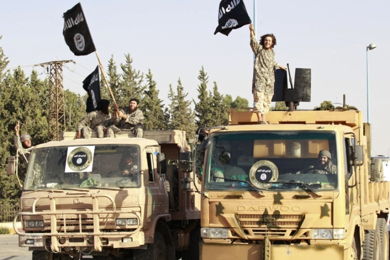 ISIL fighters wave flags as they take part in a military parade along the streets of Syria''s northern Raqqa province June 30, 2014 [Reuters]