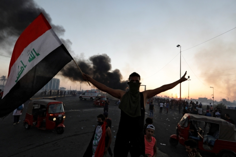 A demonstrator holds an Iraqi flag at a protest following four days of nationwide anti-government protests, in Baghdad, Iraq October 5, 2019. [Thaier Al-Sudani/Reuters]
