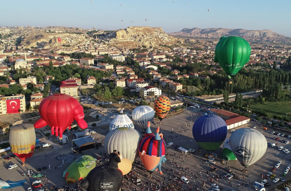 An aerial view of colourful hot air balloons in various shapes, prepared to fly over the charming touristic hub famous for its fairy chimneys as part of the International Cappadocia Hot Air Balloon Festival in Nevsehir. [Murat Oner Tas/Anadolu Agency/Getty Images]
