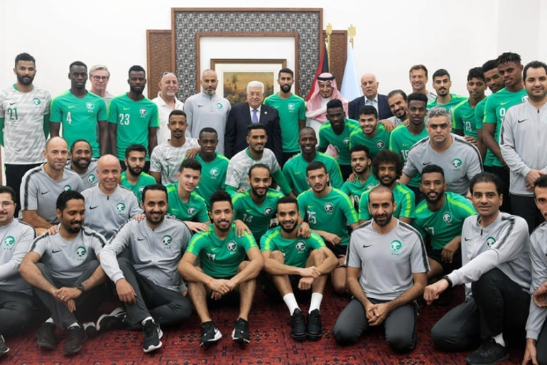 Palestinian President Mahmoud Abbas, centre, poses with the Saudi Arabia national football team in occupied West Bank city of Ramallah [Thaer Ghanaim/EPA]
