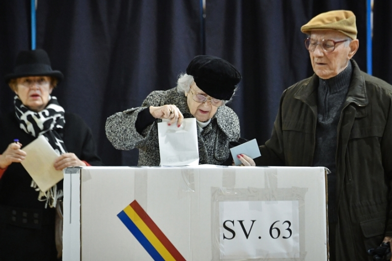 A woman casts her ballot on the second round of presidential elections at a poll station in Bucharest [Daniel Mihailescu/AFP]