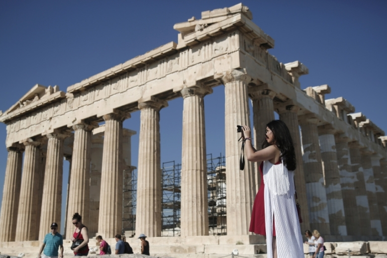 A tourist takes pictures as she stands in front of the ancient Parthenon temple on the Acropolis hill, in Athens on Tuesday, June 24, 2014. The Association of Greek Tourism Enterprises (SETE) increased its estimate for international tourist arrivals in 2014 to 19 million from 18.5 million last year [File: AP Photo/Petros Giannakouris]