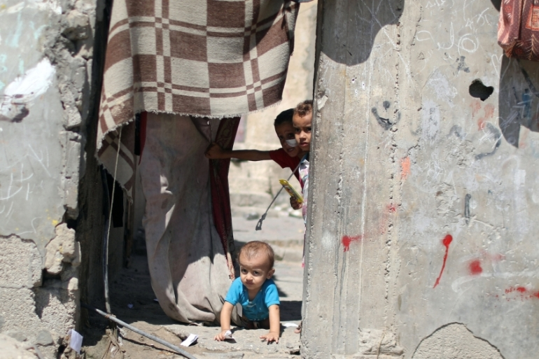 A Palestinian child crawls as other children look out of their family house in Al-Shati refugee camp in Gaza City September 25, 2019 [Mohammed Salem/Reuters]