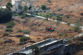 The national flags of Israel and Jordan are seen in al-Baquora in the border area between the two countries [Ronen Zvulun/Reuters]