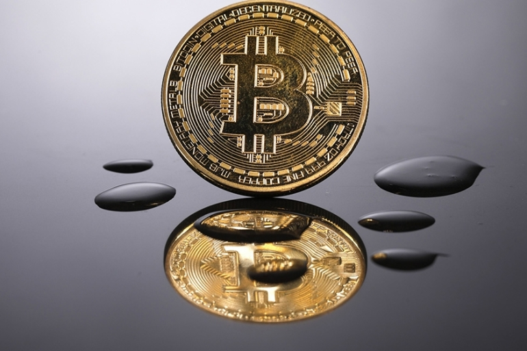 Bitcoin, the world's most-traded cryptocurrency fell as much as 11 percent on Friday before paring its losses [File: Luke MacGregor/Bloomberg]