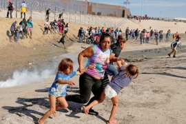Maria Meza, a migrant woman from Honduras, runs away from tear gas with her five-year-old twin daughters Saira and Cheili at the US-Mexico border on November 25, 2018 [File: Reuters/Kim Kyung-Hoon]