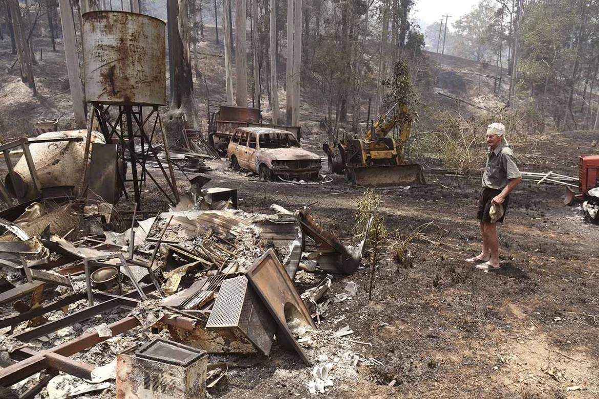 Rick Wright inspects the damage beside his house at Nabiac, New South Wales, Australia. [William West/AFP]