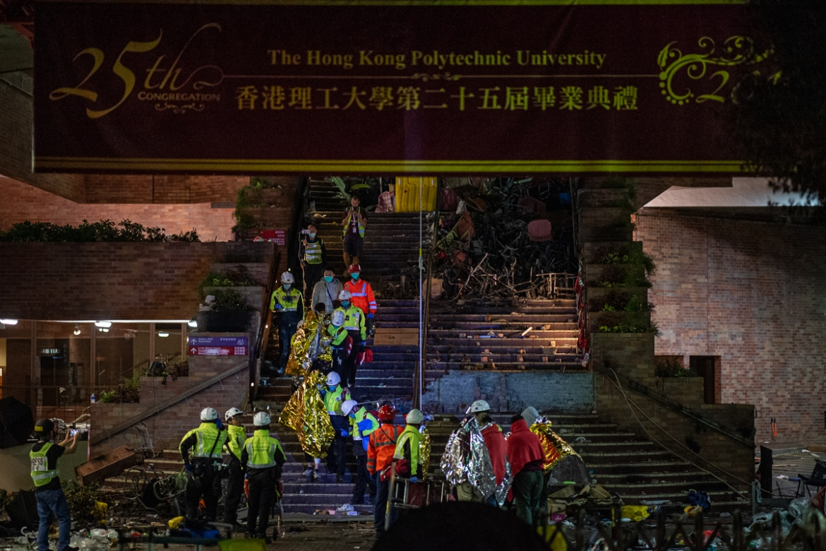 Unwell and injured protesters wrapped in emergency thermal blankets leave the campus helped by medics at the main entrance of the Hong Kong Polytechnic University (PolyU) in the Hung Hom district of Hong Kong. [Nicolas Asfouri/AFP]