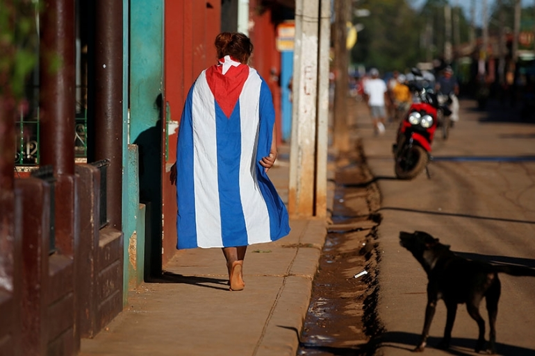 A dog barks at a person wearing a Cuban flag in the town of Alquizar, Cuba [Tomas Bravo/Reuters]