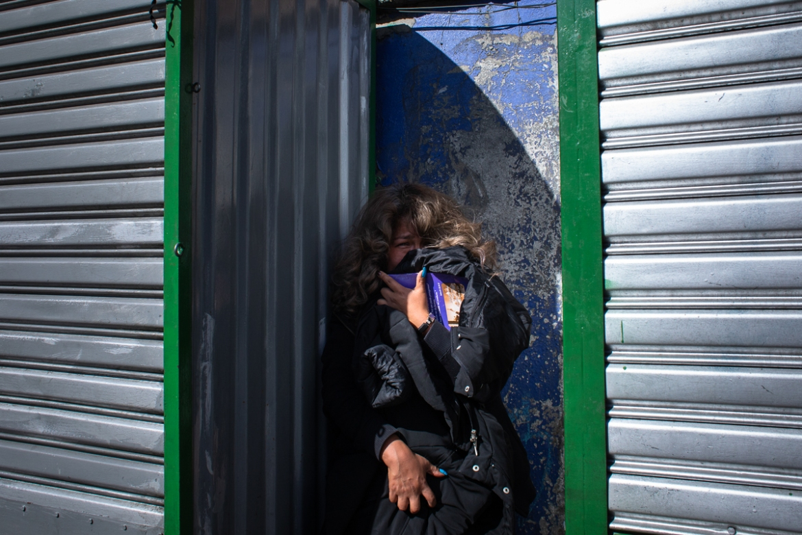 A woman hides from the violence and tear gas during violent protests in La Paz. [Erika Pineros/Al Jazeera]