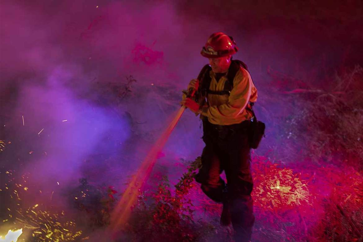 Firefighters tackling a fire in California. The US state was hit by a series of dangerous, fast-moving wildfires earlier this month as Santa Ana winds ushered in strong gusts up to 130km (81 miles) per hour and extremely low humidity. [David McNew/AFP]