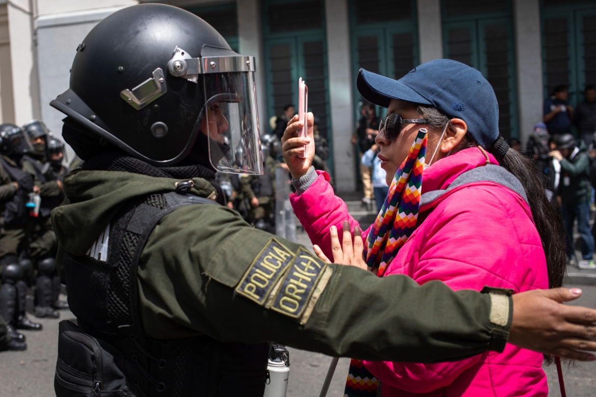 A policewoman asks a protester to step back from a barricade during demonstrations in support of former President Evo Morales in La Paz. [Erika Pineros/Al Jazeera]