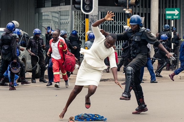 A police officer tackles a woman with his boot outside the MDC headquarters in Harare [Jekesai Njikizana/AFP]