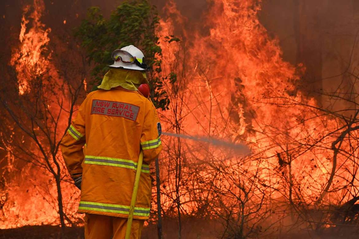 Firefighters tackle a bushfire to save a home in Taree, north of Sydney, as they try to contain dozens of blazes raging in the Australian state of New South Wales. [Peter Parks/AFP]