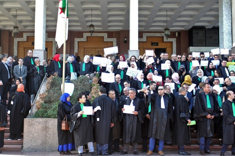 Algerian judges and prosecutors lift placards during a protest in front of the judicial council in the capital Algiers [AFP]