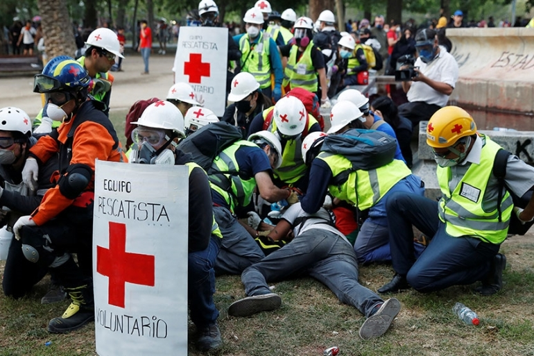 An injured demonstrator is attended to by medical personnel during a protest against Chile's government in Santiago [Jorge Silva/Reuters]