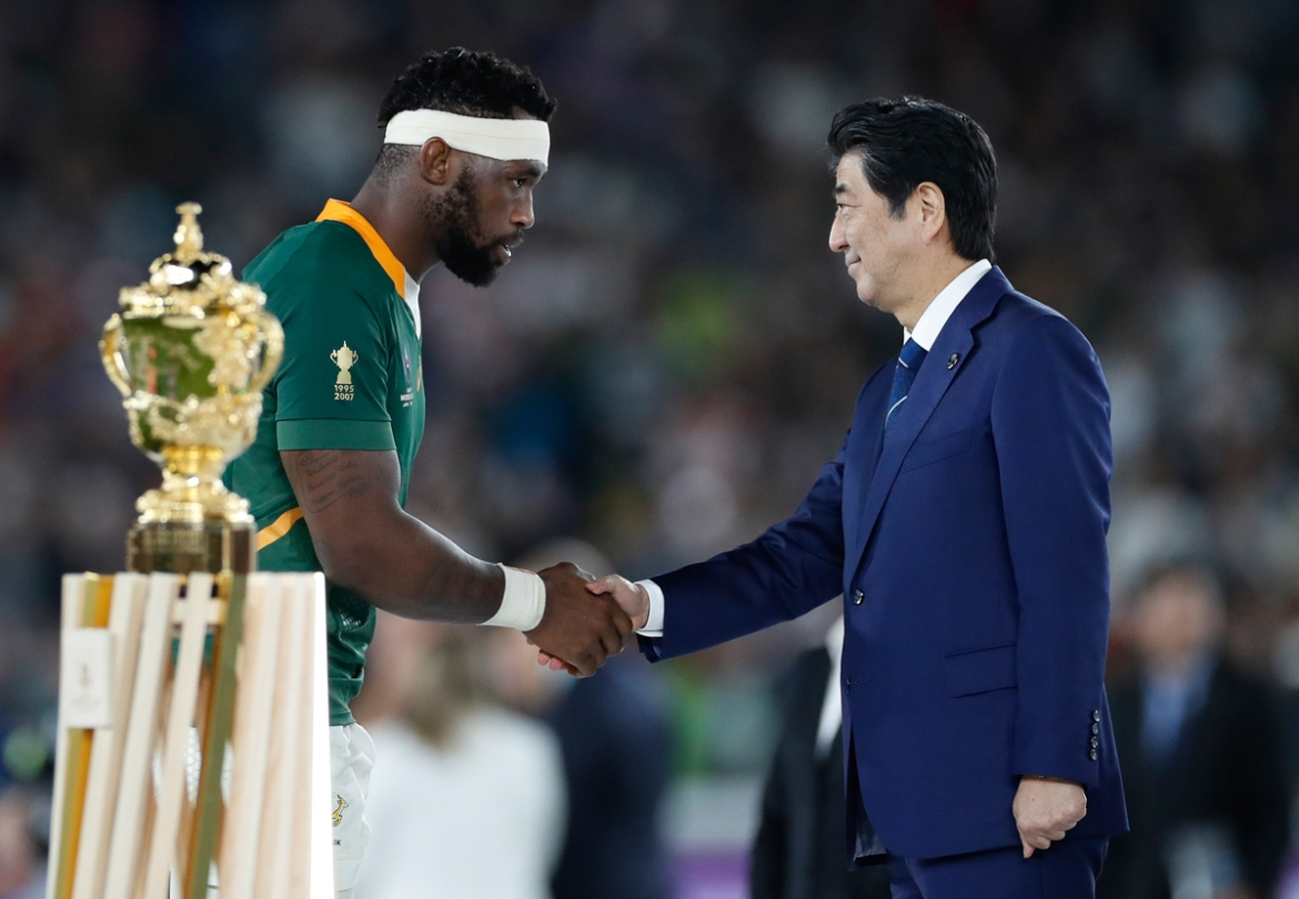 Kolisi shakes hands with Japanese Prime Minister Shinzo Abe on the podium next to the Webb Ellis Cup before the trophy presentation. [Peter Cziborra/Reuters]
