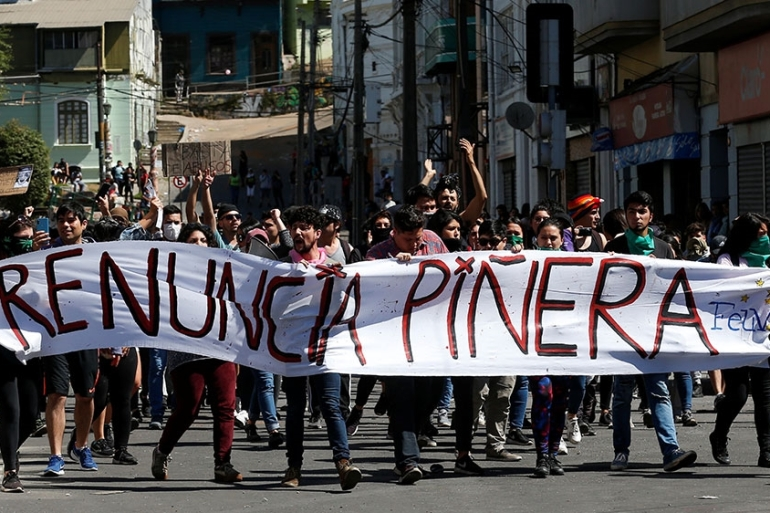 Demonstrators march while they hold a banner reading ''Pinera quit'' during a protest, in Valparaiso, Chile [File: Rodrigo Garrido/AFP]