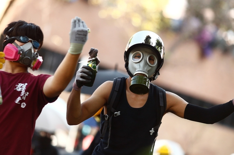 Protesters wear gas masks during clashes with police outside Hong Kong Polytechnic University in Hong Kong [Thomas Peter/Reuters]