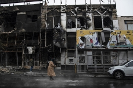 People walk past buildings burned during protests against the spike of fuel prices in the city of Karaj [Masoume Aliakbar/ISNA via AP]