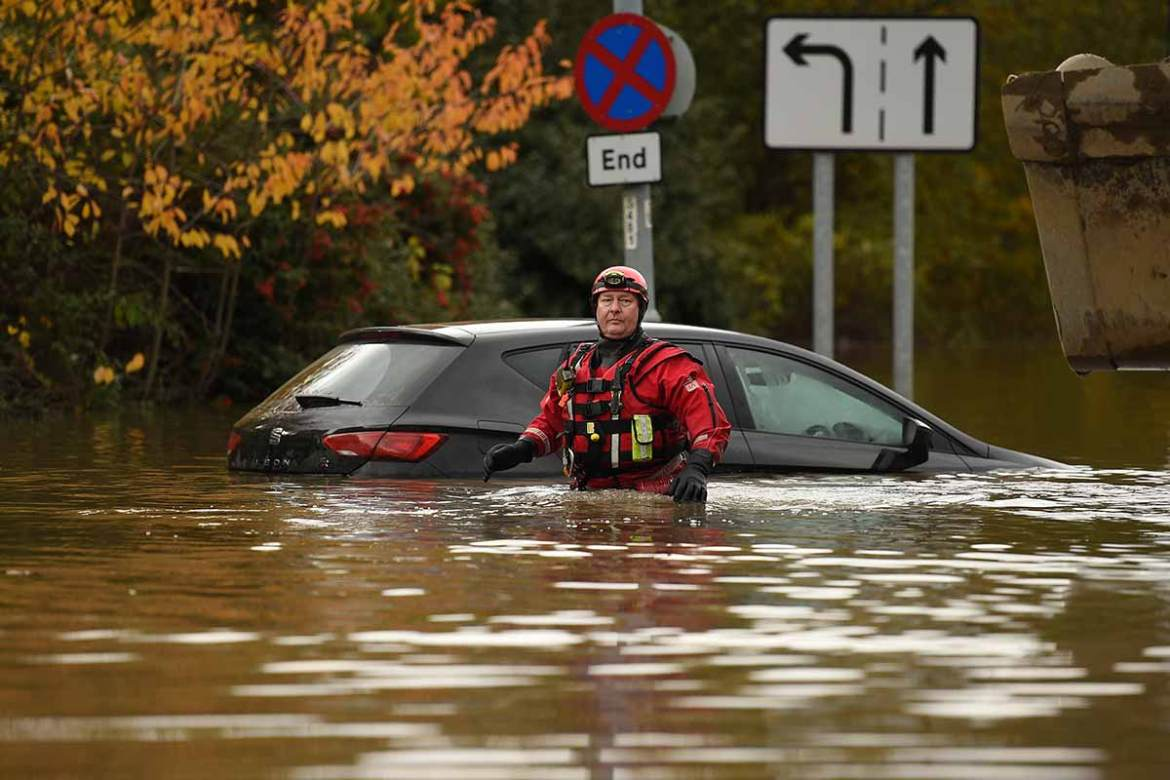 A member of the fire and rescue service wades through floodwaters in Rotherham, northern England. Over a month's worth of rain fell on parts of England in just a 24-hour period. [Oli Scarff/AFP]