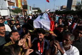 Iraqi mourners carry the coffin of a demonstrator killed at anti-government protests in Kerbala, Iraq [Abdullah Dhiaa al-Deen/Reuters]
