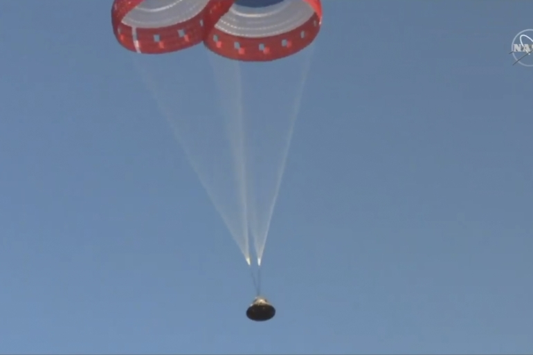 Parachutes guide the Starliner capsule to the ground after Boeing's test of its crew capsule's launch-abort system in the White Sands Missile Range [NASA/The Associated Press]