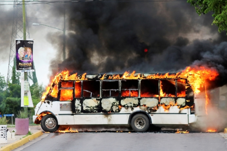 A burning bus is pictured during clashes between cartel gunmen and federal forces following the detention of Ovidio Guzman, in Culiacan, Sinaloa state, Mexico on October 17, 2019 [File: Reuters]