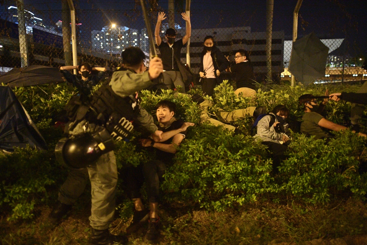 Police detain protesters and students after they tried to flee the campus. [Nicolas Asfouri/AFP]