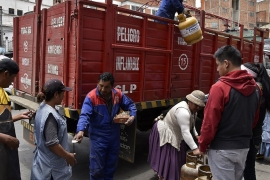 A man downloads gas cylinders for sale from a truck in La Paz [Aizar Raldes/AFP]