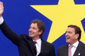 Former British Prime Minister Tony Blair waves to spectators next to Former German Chancellor Gerhard Schroeder after his arrival at the European summit in Cologne in 1999 [File: AP/Hermann Knippertz]