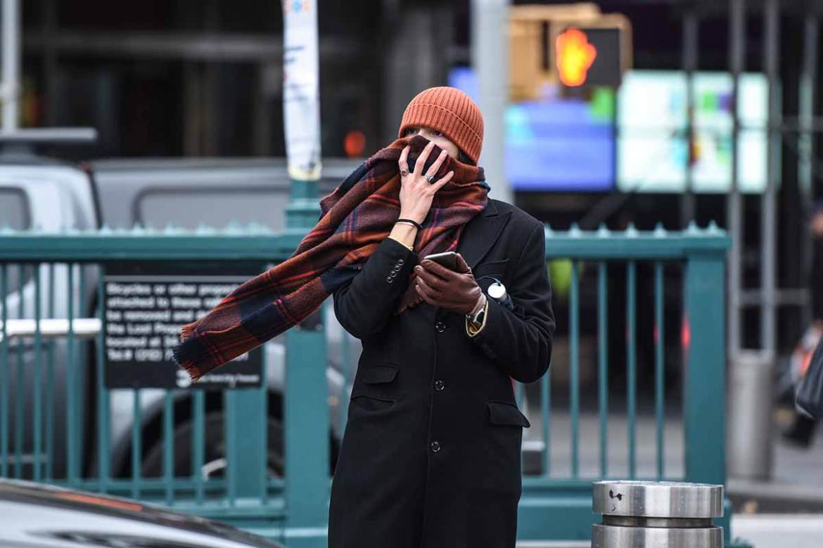 A person in New York bundles up and faces the brutal cold amid plunging temperatures due to a blast of Arctic air. [Stephanie Keith/AFP]