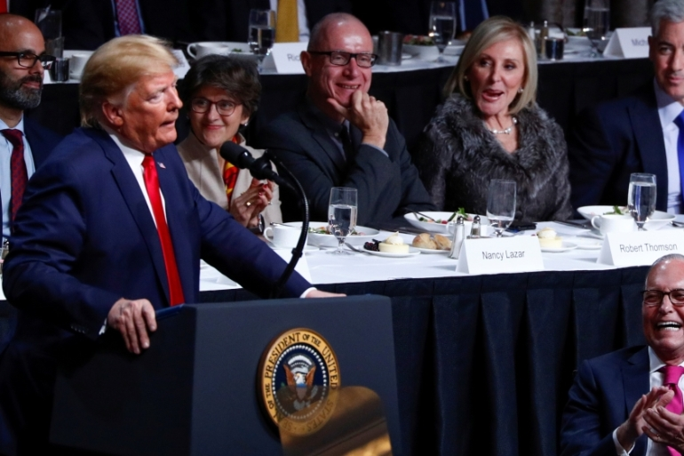 White House economic adviser Larry Kudlow laughs after United States President Donald Trump makes a joke during a speech addressing US trade with China at the Economic Club of New York in New York City [Tom Brenner/Reuters]