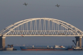 Russian jet fighters fly over a bridge connecting Russia with Crimea with a cargo ship blocking passage [File: Pavel Rebrov/Reuters]