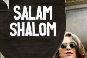 A woman displays poster demanding 'Salam, Shalom' (peace, peace) during a demonstration for peace in Palestine in Zurich on July 29, 2014 [Reuters/Arnd Wiegmann]